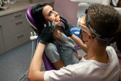 Η νέα γυναίκα ελέγχει τα δόντια στο οδοντικό γραφείο Ο αρσενικός οδοντίατρος εξετάζει Στοκ φωτογραφίες με δικαίωμα ελεύθερης χρήσης