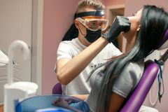 Η νέα γυναίκα ελέγχει τα δόντια στο οδοντικό γραφείο Ο αρσενικός οδοντίατρος εξετάζει Στοκ φωτογραφία με δικαίωμα ελεύθερης χρήσης