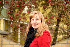 Η νέα γυναίκα ενάντια σε ένα Apple-δέντρο με τα κόκκινα μήλα Στοκ Εικόνες