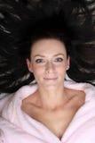 Η νέα γυναίκα εναπόκειται στο τρίχωμα που τοποθετείται γύρω από το κεφάλι της Στοκ Φωτογραφίες