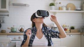 Η νέα γυναίκα εξετάζει τα γυαλιά εικονικής πραγματικότητας στην κουζίνα στο σπίτι απόθεμα βίντεο