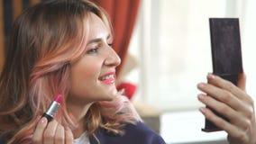 Η νέα γυναίκα εξετάζει την σε έναν καθρέφτη τσεπών και ρυθμίζει makeup απόθεμα βίντεο