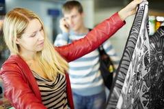 Η νέα γυναίκα εξετάζει το ζωηρόχρωμο ύφασμα Στοκ Εικόνες