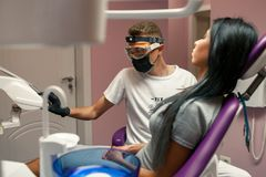 Η νέα γυναίκα εξετάζεται από το γιατρό στο οδοντικό γραφείο Αρσενικός οδοντίατρος Στοκ Εικόνες