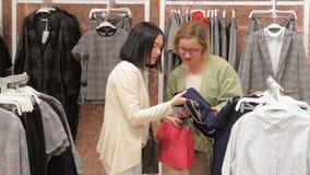 Η νέα γυναίκα επιλέγει ένα φόρεμα σε ένα κατάστημα ιματισμού και συσκέπτεται με το φίλο της Προσπάθεια στα φορέματα στον καθρέφτη απόθεμα βίντεο
