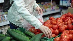Η νέα γυναίκα επιλέγει τις ώριμες κόκκινες ντομάτες αγοράζοντας τα φρέσκα λαχανικά σε μια υπεραγορά απόθεμα βίντεο