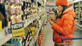 Η νέα γυναίκα επιλέγει τα τρόφιμα στη μεγάλη υπεραγορά Το κορίτσι στέκεται κοντά στο ράφι και επιλέγει τα προϊόντα Χρώμα που βαθμ φιλμ μικρού μήκους