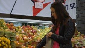 Η νέα γυναίκα επιλέγει τα φρούτα στο φυτικό τμήμα υπεραγορών απόθεμα βίντεο