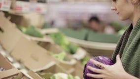Η νέα γυναίκα επιλέγει το λάχανο στα ράφια μαγαζιό απόθεμα βίντεο