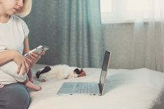 Η νέα γυναίκα εργάζεται από το σπίτι, που κρατά το μωρό στην περιτύλιξη, η γάτα βρίσκεται πλησίον στοκ φωτογραφίες