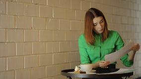 Η νέα γυναίκα εργάζεται με τα αρχιτεκτονικά σχέδια απόθεμα βίντεο