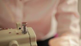 Η νέα γυναίκα εργάζεται σε μια ράβοντας μηχανή σε ένα εργοστάσιο ιματισμού seamstress Σχεδιαστής μόδας απόθεμα βίντεο