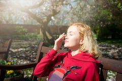 Η νέα γυναίκα εφαρμόζει sunscreen στο πρόσωπό της καθμένος στον πάγκο στο πάρκο στοκ φωτογραφία με δικαίωμα ελεύθερης χρήσης