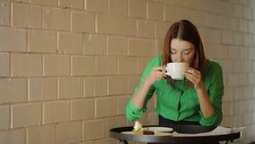 Η νέα γυναίκα ελέγχει τα σχεδιαγράμματα πίνοντας τον καφέ, που λειτουργεί με τα αρχιτεκτονικά σχέδια φιλμ μικρού μήκους