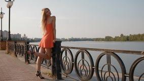 Η νέα γυναίκα θέτει στο φωτογράφο κοντά στον ποταμό απόθεμα βίντεο