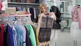 Η νέα γυναίκα θαυμάζει και εμπνεσμένος από τους σχεδιαστές το φόρεμα σε μια αίθουσα εκθέσεως να ανταλλάξει τη λεωφόρο, τη λήψη απ φιλμ μικρού μήκους
