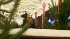 Η νέα γυναίκα θαυμάζει τα φω'τα Χριστουγέννων στην οδό Το θηλυκό εξετάζει τις διακοσμήσεις cafee υπαίθρια απόθεμα βίντεο