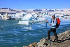 Η νέα γυναίκα θαυμάζει την ομορφιά της παγετώδους λιμνοθάλασσας Jokulsarlon Στοκ Φωτογραφία