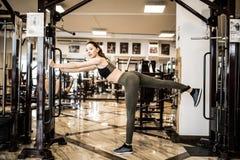 Η νέα γυναίκα ικανότητας εκτελεί την άσκηση με τη διασταύρωση καλωδίων άσκηση-μηχανών στη γυμναστική Στοκ Φωτογραφία