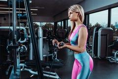 Η νέα γυναίκα ικανότητας εκτελεί την άσκηση με τη διασταύρωση καλωδίων άσκηση-μηχανών στη γυμναστική Στοκ φωτογραφίες με δικαίωμα ελεύθερης χρήσης