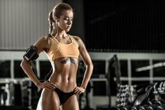 Η νέα γυναίκα ικανότητας που κουράζεται στη γυμναστική και ακούει μουσική με την κάσκα Στοκ Εικόνα