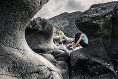 Η νέα γυναίκα κάθεται μεταξύ των πετρών καμπυλών στη Νορβηγία Στοκ φωτογραφία με δικαίωμα ελεύθερης χρήσης