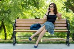 Η νέα γυναίκα κάθεται σε έναν πάγκο και μιλά σε ένα samrtphone Στοκ φωτογραφίες με δικαίωμα ελεύθερης χρήσης