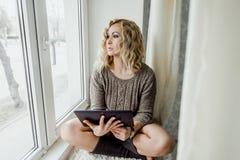 Η νέα γυναίκα κάθεται σε ένα παράθυρο και μια εκμετάλλευση μια ταμπλέτα στοκ φωτογραφία με δικαίωμα ελεύθερης χρήσης