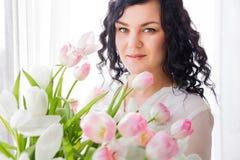 Η νέα γυναίκα κάθεται σε ένα παράθυρο με μια ανθοδέσμη των λουλουδιών στοκ εικόνες με δικαίωμα ελεύθερης χρήσης