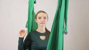 Η νέα γυναίκα κάθεται σε μια αιώρα που παρουσιάζει αντίο σημάδι Εναέριος εκπαιδευτής ικανότητας μυγών aero workout Meditates, αρμ απόθεμα βίντεο