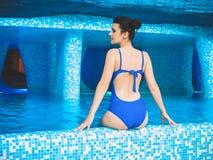 Η νέα γυναίκα κάθεται στην άκρη της λίμνης με το νερό εσωτερικό swimpool aquapark χαριτωμένη πισίνα συνεδρίασης κοριτσιών πλησίον Στοκ φωτογραφία με δικαίωμα ελεύθερης χρήσης