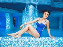 Η νέα γυναίκα κάθεται στην άκρη της λίμνης με το νερό εσωτερικό swimpool aquapark χαριτωμένη πισίνα συνεδρίασης κοριτσιών πλησίον Στοκ εικόνες με δικαίωμα ελεύθερης χρήσης