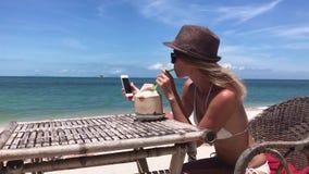 Η νέα γυναίκα κάθεται στην παραλία με το ποτό smartphone που μια καρύδα ποτίζει απόθεμα βίντεο