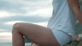 Η νέα γυναίκα κάθεται στην παραλία στο θερινό βράδυ υπαίθρια φιλμ μικρού μήκους
