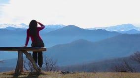Η νέα γυναίκα κάθεται στον πάγκο εξωτερικό και εξετάζει το εικονογραφικό τοπίο με τα βουνά απόθεμα βίντεο