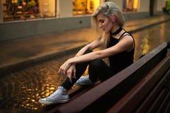 Η νέα γυναίκα κάθεται στον υγρό πάγκο στην οδό πόλεων το βράδυ στη βροχή Στοκ εικόνες με δικαίωμα ελεύθερης χρήσης