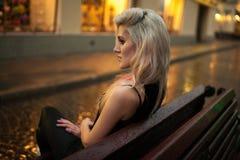 Η νέα γυναίκα κάθεται στον υγρό πάγκο στην οδό πόλεων το βράδυ στη βροχή Στοκ φωτογραφία με δικαίωμα ελεύθερης χρήσης