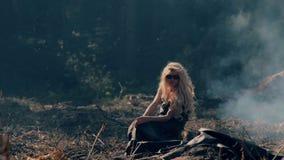 Η νέα γυναίκα κάθεται στο έδαφος που καίει πλησίον το δάσος απόθεμα βίντεο