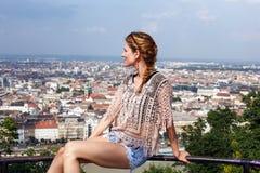Η νέα γυναίκα κάθεται στο κιγκλίδωμα απολαμβάνοντας το πανόραμα της Βουδαπέστης Στοκ Φωτογραφίες