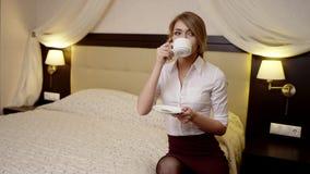 Η νέα γυναίκα κάθεται στο κρεβάτι και πίνει ένα φλυτζάνι του τσαγιού απόθεμα βίντεο