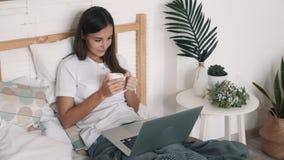Η νέα γυναίκα κάθεται στο κρεβάτι, πίνει το τσάι και προσέχει τον κινηματογράφο στο lap-top, σε αργή κίνηση απόθεμα βίντεο