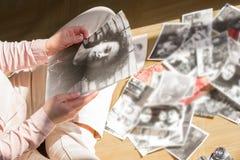 Η νέα γυναίκα κάθεται στο πάτωμα και εξετάζει τις γραπτές φωτογραφίες στοκ εικόνες