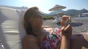 Η νέα γυναίκα κάνει κάτι με το τηλέφωνό του στην παραλία απόθεμα βίντεο