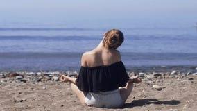 Η νέα γυναίκα κάνει την περισυλλογή στο λωτό να θέσει στη θάλασσα/την ωκεάνια παραλία, την αρμονία και το σχέδιο Όμορφη γιόγκα άσ φιλμ μικρού μήκους