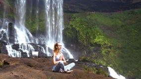 Η νέα γυναίκα κάνει τις ασκήσεις γιόγκας pranayama στο μεγάλο βράχο απόθεμα βίντεο