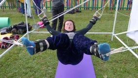 Η νέα γυναίκα κάνει τις ασκήσεις στις συσκευές κατάρτισης στο πάρκο υπαίθρια φιλμ μικρού μήκους