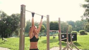Η νέα γυναίκα κάνει τις διάφορες bodyweight ασκήσεις στον οριζόντιο φραγμό απόθεμα βίντεο