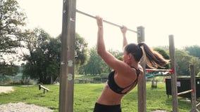 Η νέα γυναίκα κάνει τις διάφορες bodyweight ασκήσεις στον οριζόντιο φραγμό φιλμ μικρού μήκους