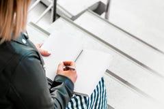 Η νέα γυναίκα κάνει τις σημειώσεις στο ιώδες σημειωματάριο στη βιβλιοθήκη και τη συνεδρίαση στα βήματα σκαλών στοκ φωτογραφίες