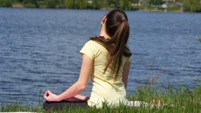 Η νέα γυναίκα κάνει το κεφάλι κάμψεων ασκήσεων μπρος πίσω Συνεδρίαση κοριτσιών στη χλόη και meditate εκτός από τον ποταμό που κάν φιλμ μικρού μήκους